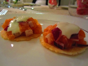 Salmon, red onion, and sour cream on the top of crackers, for entree
